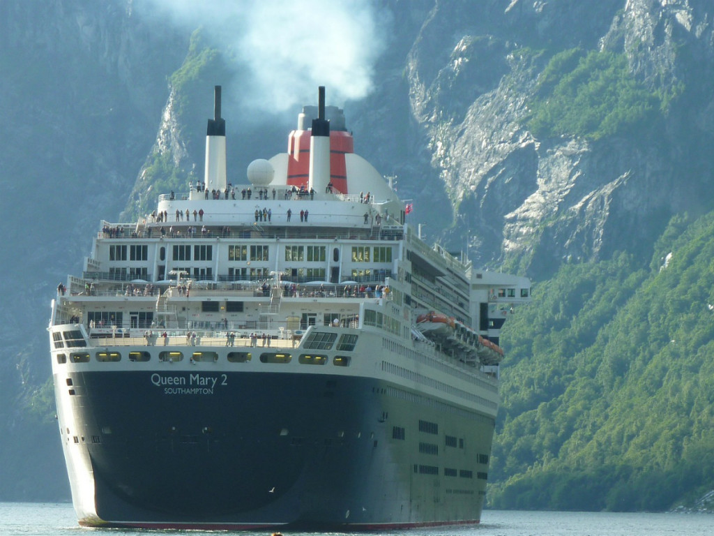cruise ship queen mary 2 sailing into harbour with tall cliffs