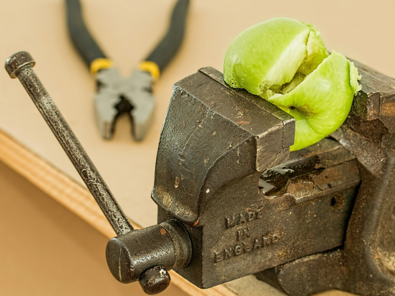 table mounted wrench squashing an apple