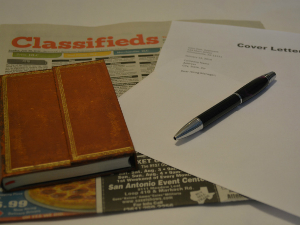 book, newspaper and pen on top of curriculum vitae