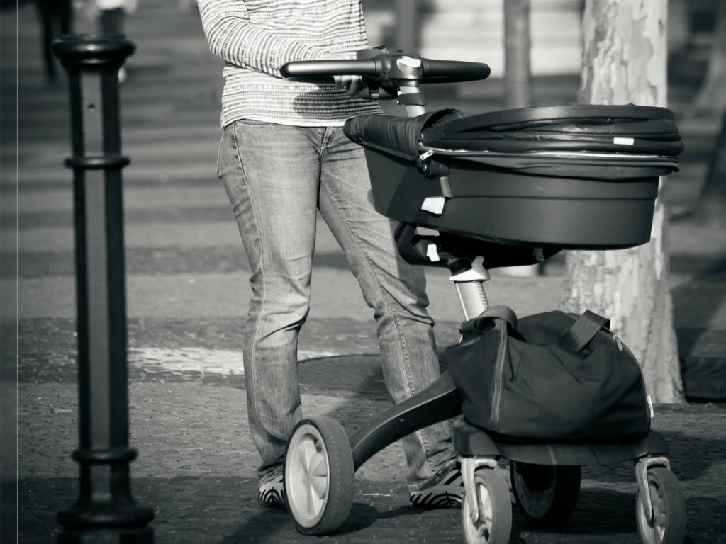 mother pushing modern pram on the street