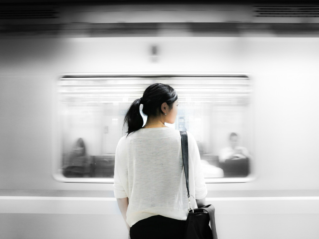 photo of woman waiting for train